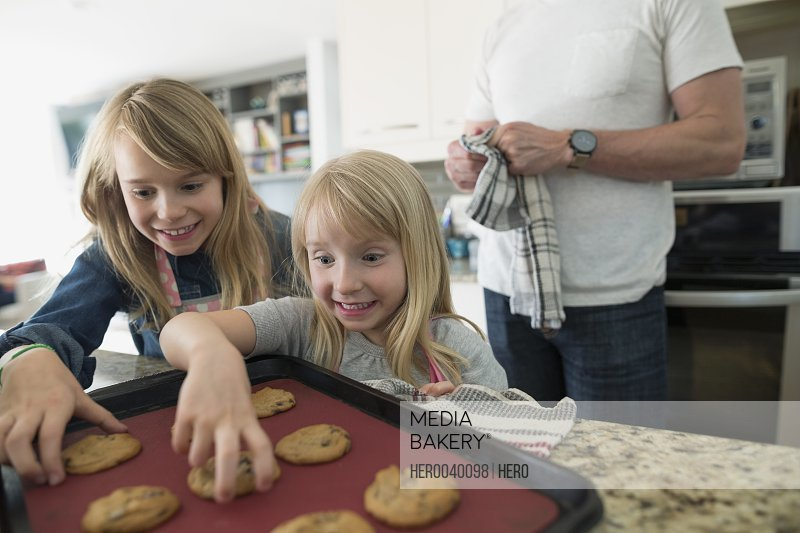 Excited girls reaching for fresh baked cookies in kitchen