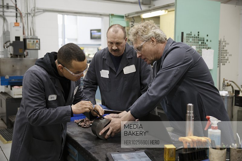 Male machinists examining equipment in factory