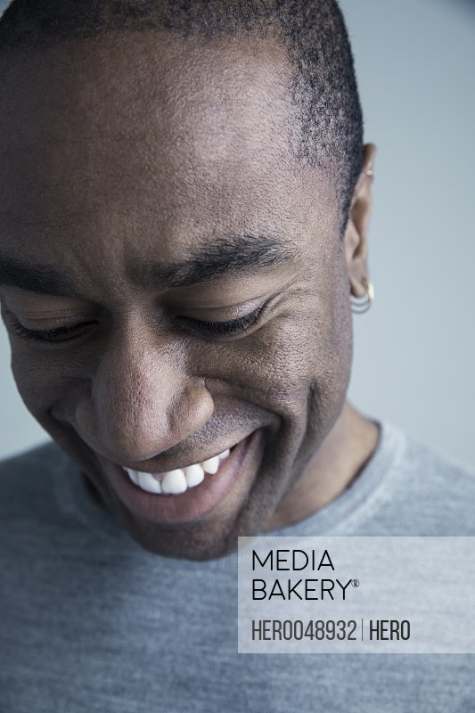 Close up portrait smiling African American man wearing earring looking down