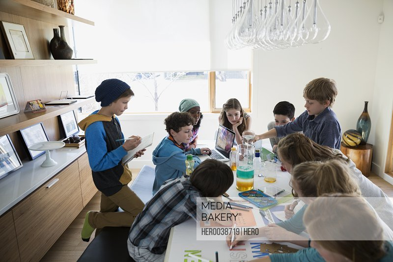 Boys and girls conducting science experiment dining table
