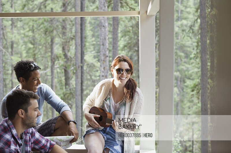 Woman playing ukulele for friends on cabin porch