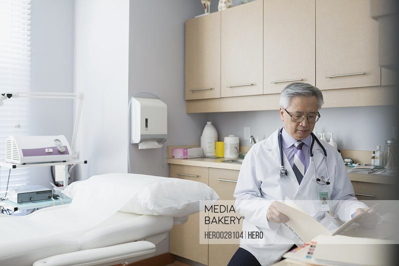 Doctor reviewing medical records in examination room