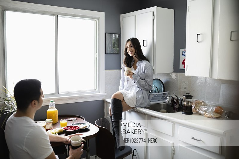 Young Latinx couple talking and drinking coffee in morning kitchen