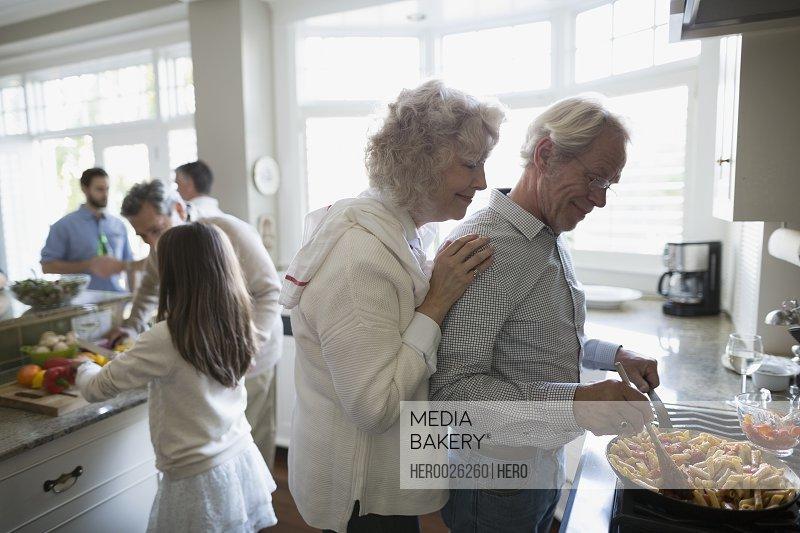 Senior couple cooking at kitchen stove