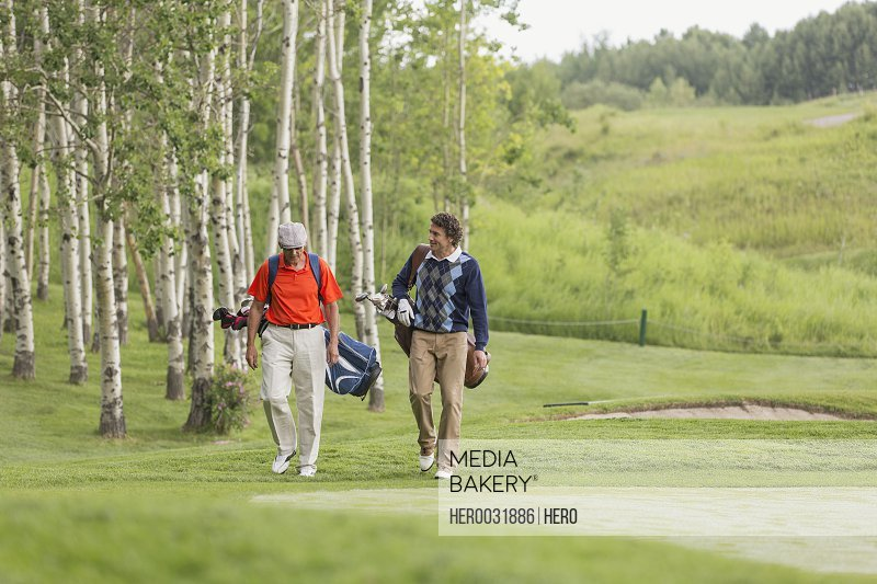 golfers having a conversation as they walk on golf course