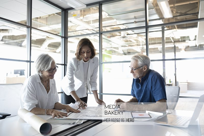 Clients discussing plans with design professional in studio