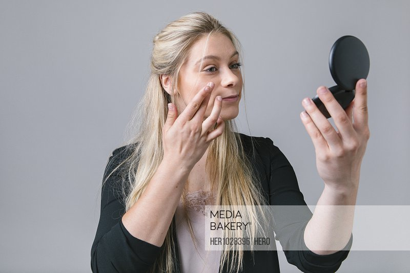 Young woman checking makeup with compact mirror