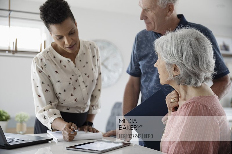 Financial advisor with digital tablet talking to senior couple