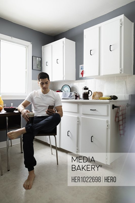 Barefoot young Latinx man using smart phone in breakfast kitchen