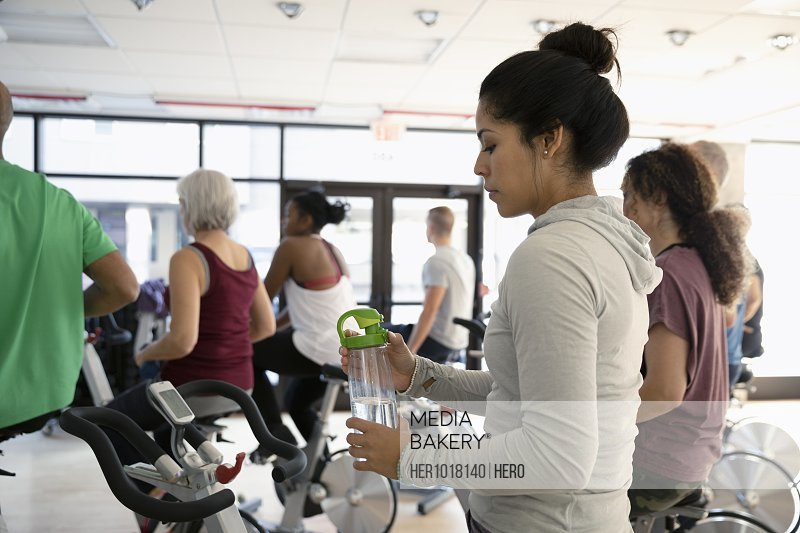 Woman with water bottle preparing for spin class in gym