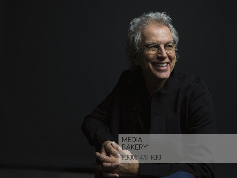 Portrait smiling senior an with gray hair and eyeglasses looking away against black background