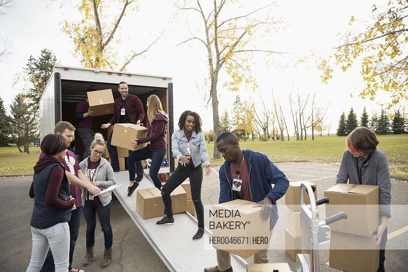 Volunteers loading cardboard boxes onto truck