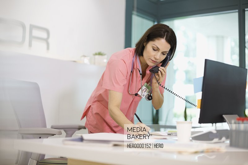 Female nurse writing notes during phone call
