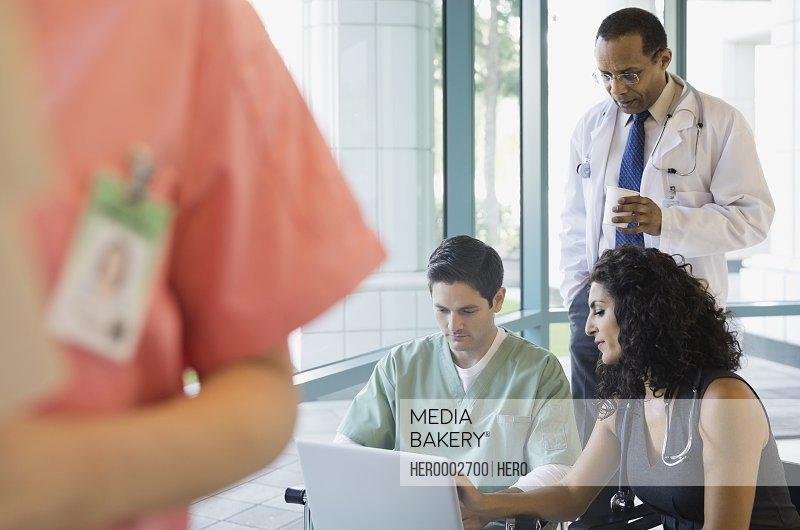 Medical team using laptop in hospital