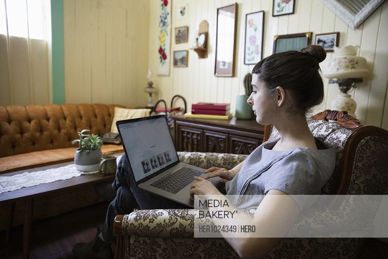 Woman online shopping at laptop in living room