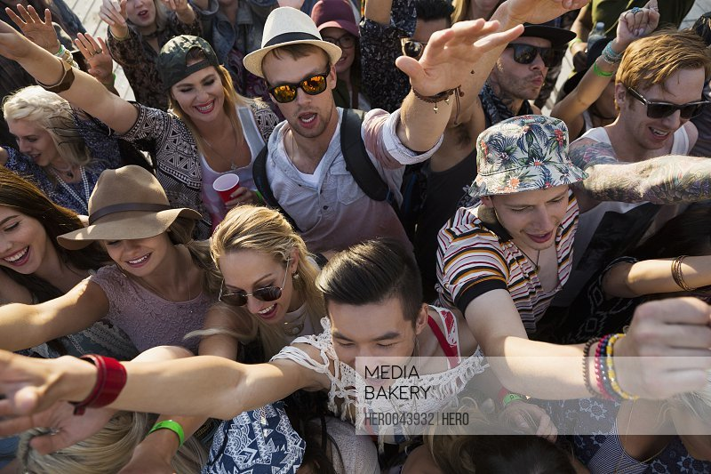 Young crowd cheering at summer music festival