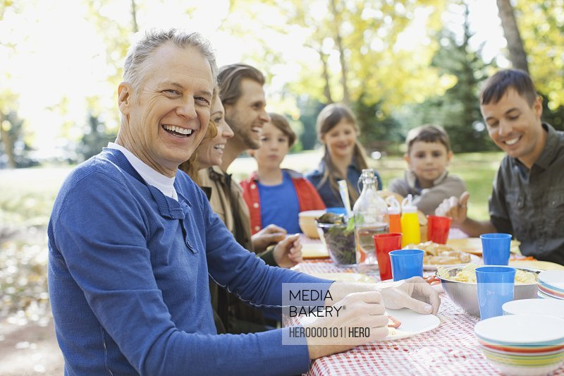 Portrait of happy mature man with family enjoying meal in park