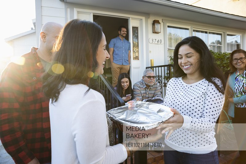 Latinx woman delivering casserole to neighbor