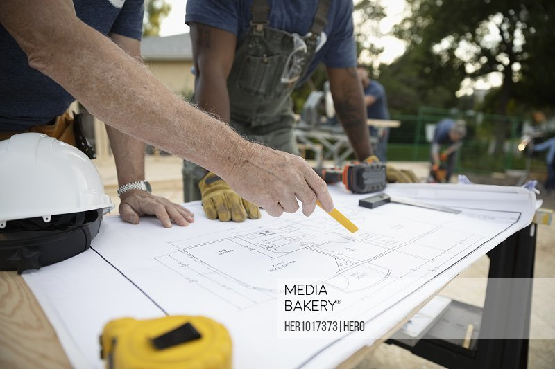 Male architect volunteers reviewing blueprints, building house