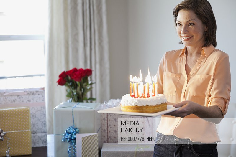 Smiling woman holding birthday cake at home