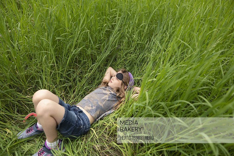 Serene girl in pirate costume laying in tall grass
