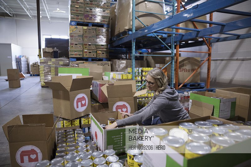 Female volunteer filling donation box with canned food for food drive in warehouse