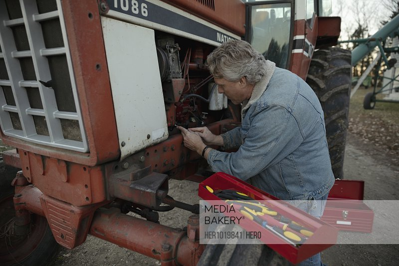 Male farmer with tools fixing tractor