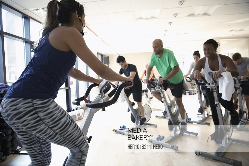 Female instructor on exercise bike leading spin class in gym
