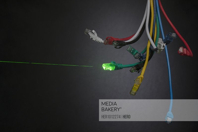 Green laser from contrasting multicolor computer cables dangling in bundle