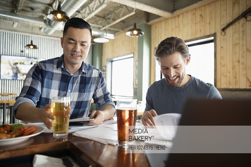 Male business owners working and drinking beer in brewhouse