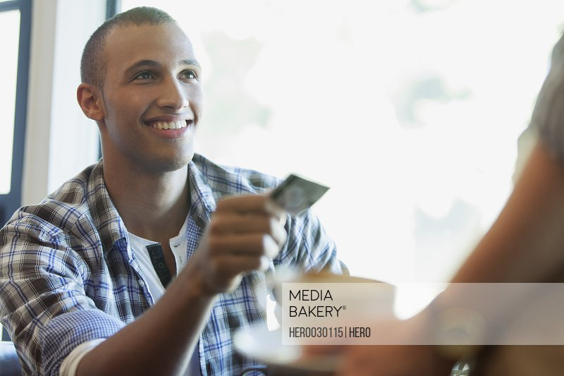 Young adult man handing credit card to server at coffee shop