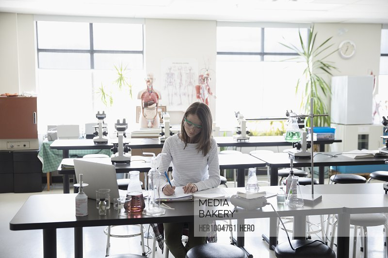 Girl middle school student conducting scientific experiment in science laboratory