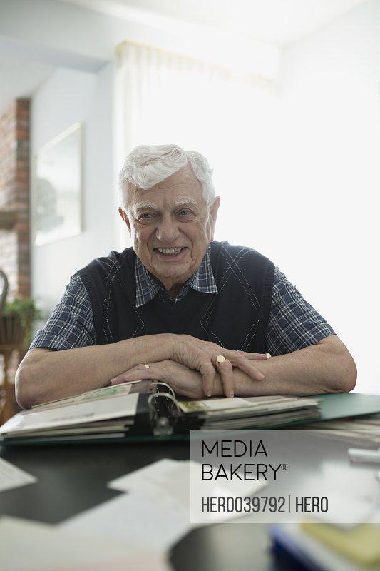 Portrait smiling senior man looking through photograph album