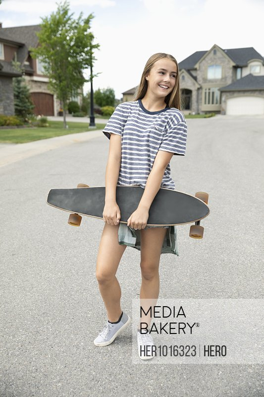 Tween girl with skateboard on neighborhood street