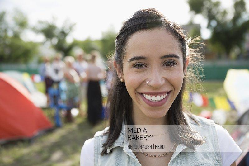 Portrait smiling young brunette woman at summer music festival campsite
