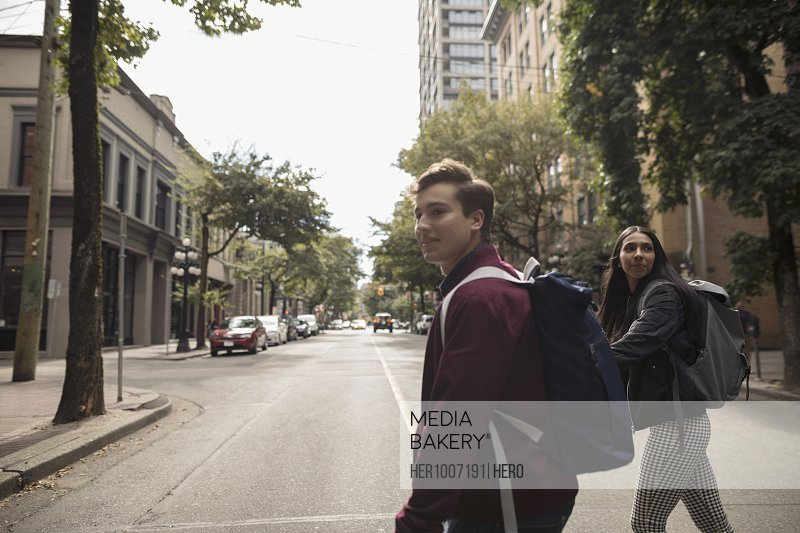 Young couple with backpacks crossing urban street