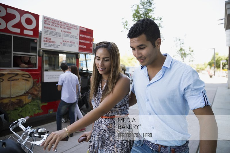 Couple with bicycle walking outside food truck