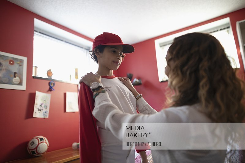 Latinx mother helping son get dressed for baseball practice in bedroom