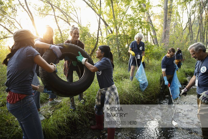People volunteering, cleaning up garbage and tire in stream