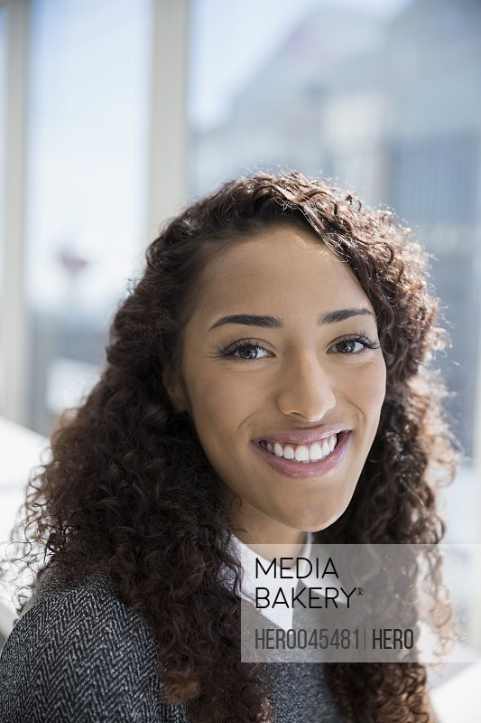 Close up portrait smiling businesswoman with curly hair