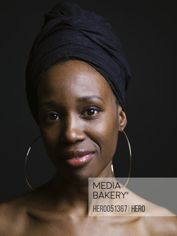 68f45cd456683 Photo by Hero Images - Portrait confident African American woman wearing  headscarf and hoop earrings against black background