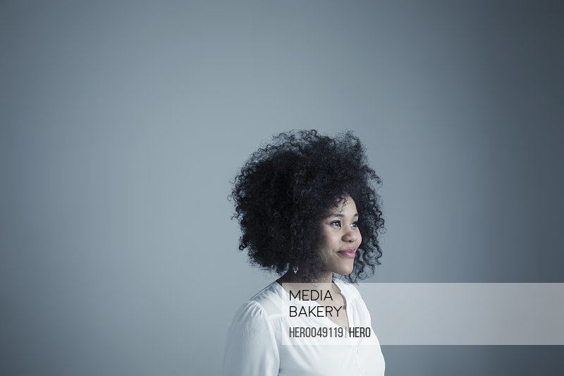 Portrait smiling mixed race young woman with curly black afro hair looking away