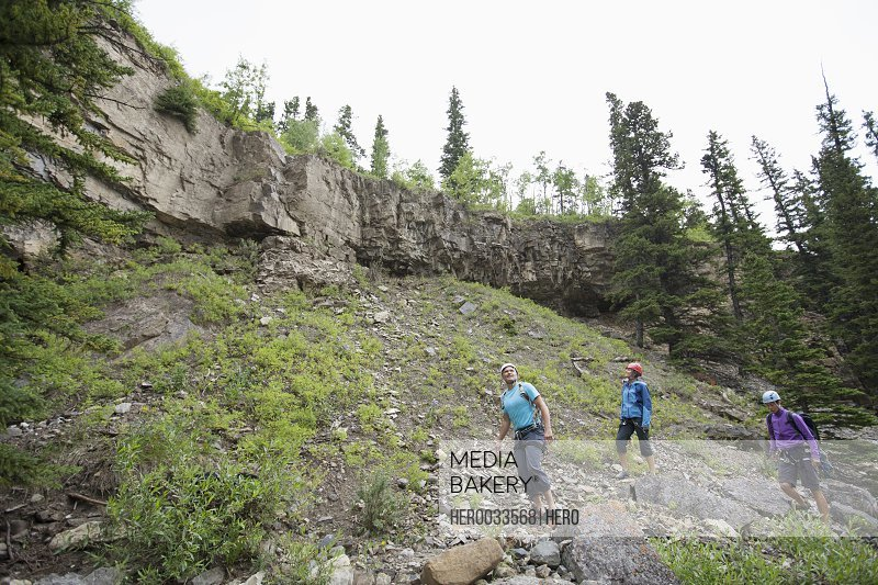 three rock climbers scouting out area to climb