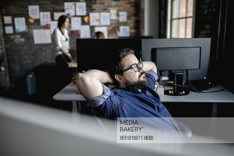 Thoughtful creative businessman looking away in office