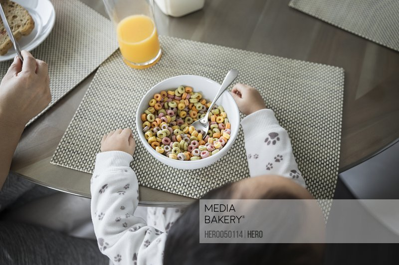 Overhead view toddler boy eating cereal at breakfast table
