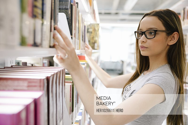 Student wearing glasses selecting book from library shelf