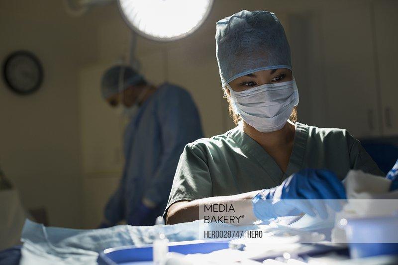 Plastic surgeon preparing equipment in operating room