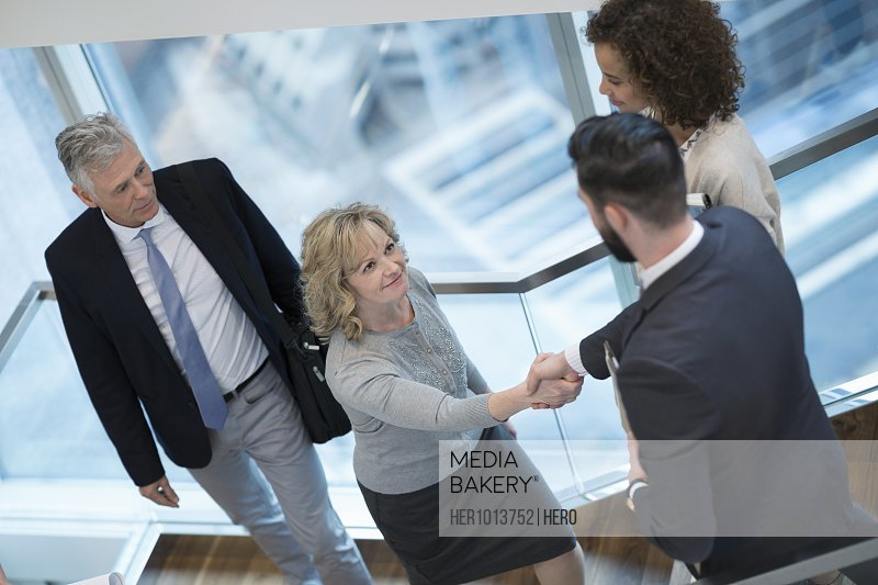 Business people handshaking on staircase