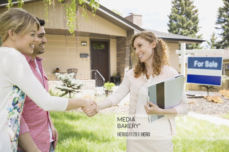 Realtor and couple handshaking outside house