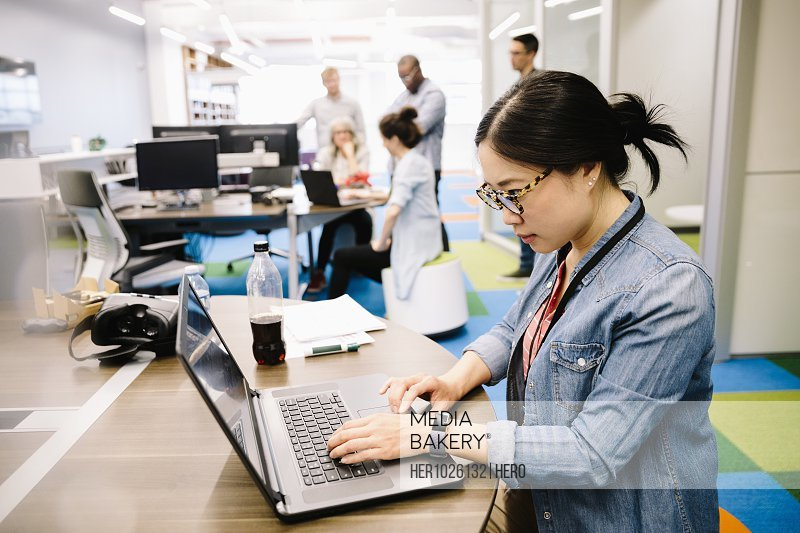 Creative businesswoman working at laptop in open plan office